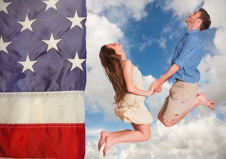 cross legged: Digital composite of Couple jumping in the sky against american flag
