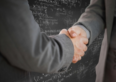 coworker: Digital composite of Handshake against grey wall with math doodles
