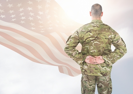 Digital composite of Back view of soldier in front of white background with american flag Stock Photo