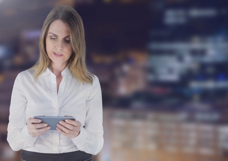 Digital composite of Businesswoman using a digital tablet against buildings in background