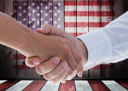 extending: Digital composite of People shaking their hands against american flag Stock Photo
