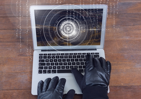 stealer: Digital composite of Gloved hands typing on a laptop on a wood table