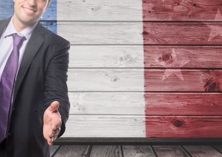 extending: Digital composite of Business man shaking his hands against french flag Stock Photo