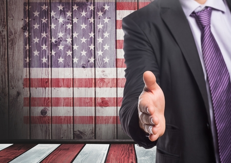 Digital composite of Business man shaking his hand against american flag