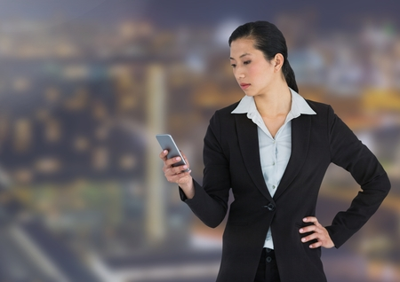 well dressed: Digital composite of Businesswoman texting against buildings in background