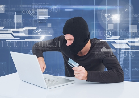 cross legged: Digital composite of Hacker using a laptop and holding a credit card in front of 3D digital background Stock Photo