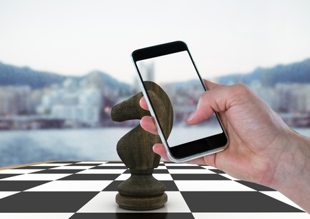 tactics: Digital composite of Hand with device against 3D chess piece and blurry skyline