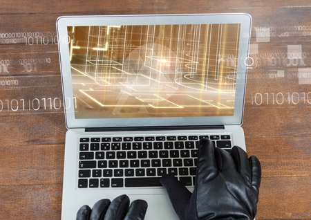 stealer: Digital composite of hands with gloves using a laptop in a wood table