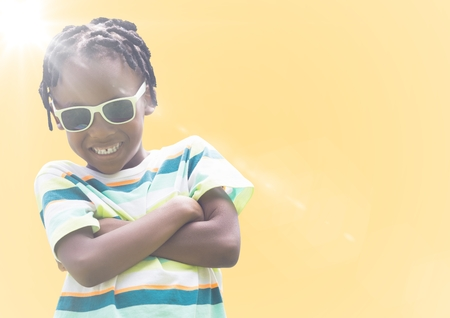 Digital composite of Boy in sunglasses arms folded against yellow background with flare
