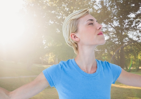 Digital composite of Close up of woman with arms outstretched against blurry park with flare