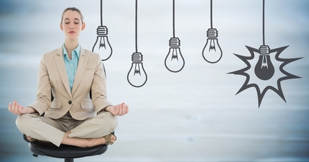swivel: Digital composite of Business woman meditating against blurry blue wood panel and 3D grey lightbulb graphic