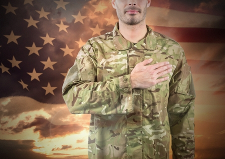 grasslands: Digital composite of Military with hand on his heart against sunset and american flag