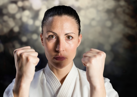 Digital composite of Woman in karate suit against bokeh Stock Photo
