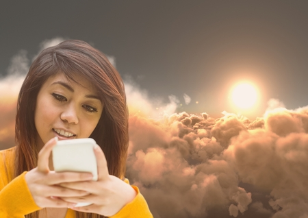 Digital composite of Woman Texting in 3D clouds with sunset