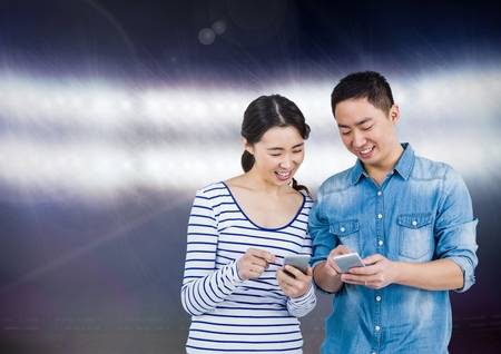 Digital composite of Smiling couple texting against shiny background