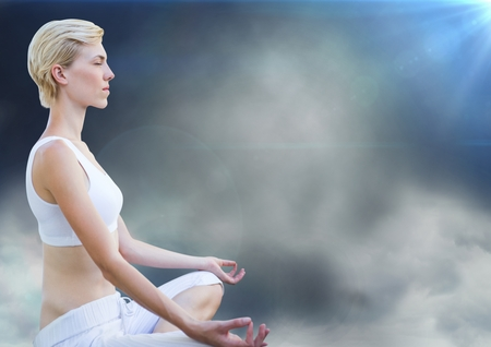 Digital composite of Woman meditating against clouds and flares Stock Photo