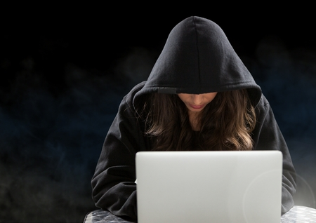 composite: Digital composite of Woman hacker working on laptop in front of black background