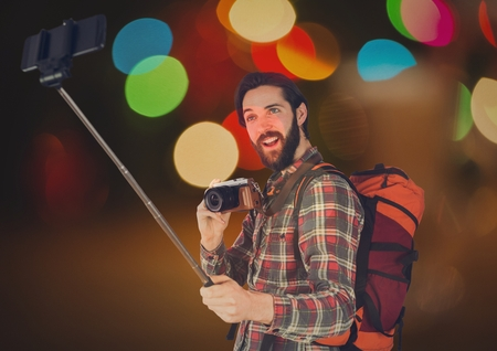 Digital composite of Tourist taking selfie  with his camera  and his phone against glowing background Stock Photo