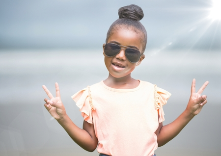 Digital composite of Girl in sunglasses making peace signs against blurry beach with flare