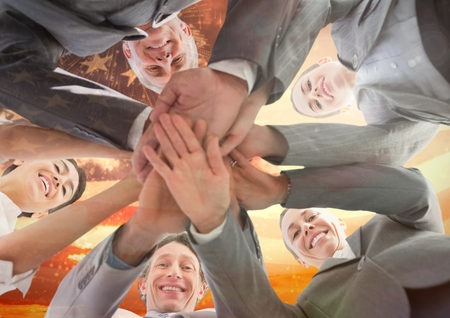 well dressed: Digital composite of colleagues with hands together against american flag