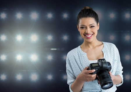 black and white photograph: Digital composite of photographer smiling  looking to the photos on camera .stadium lights  background Stock Photo