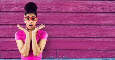 Digital composite of Surprised woman standing on a pink wooden background Stock Photo