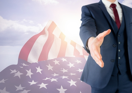 Digital composite of Business man shaking his hand against 3D american flag Stock Photo