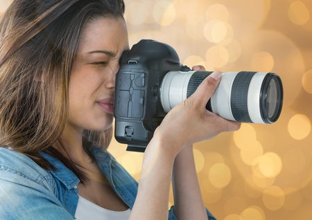 stealer: Digital composite of young photographer taking a photo (foreground). Gold bokeh background