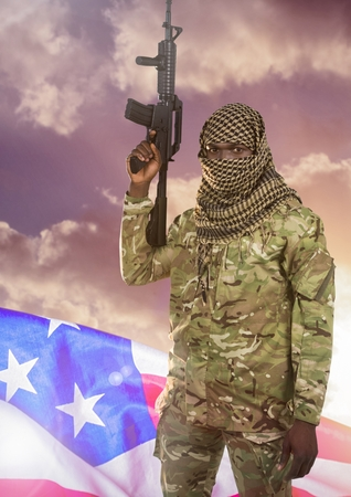 Digital composite of Soldier with weapon in front of american flag and clouds Stock Photo