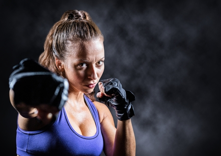 punching: Digital composite of Female boxer against mist