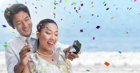 abode: Digital composite of Confetti and man proposing to woman against blurry beach