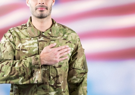Digital composite of Part of a soldier with hand on the heart against fluttering american flag