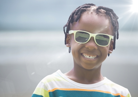 Digital composite of Close up of boy in sunglasses against blurry beach with flare