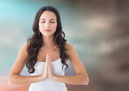 Digital composite of Woman meditating against blurry blue and brown background