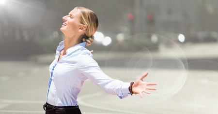 Digital composite of Business woman arms outstretched against blurry street with flare Stock Photo