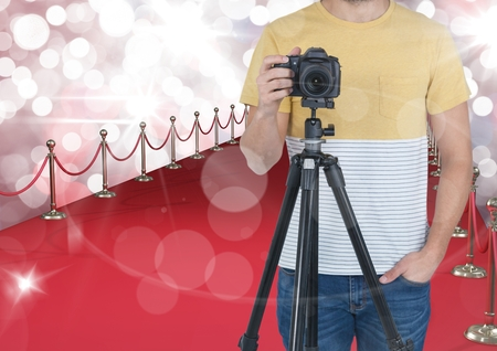 Digital composite of photographer with camera on tripod in the red carpet. Red and white bokeh background and flares ever