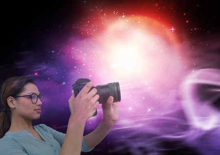 Digital composite of Photographer taking pictures against galaxy background Stock Photo