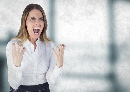 Digital composite of Angry business woman against blurry grey office with grunge overlay