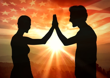 Digital composite of Silhouette of people high fiving against sunset and american flag