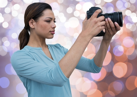 composite: Digital composite of young photographer taking a photo. Blue, orange and white bokeh background Stock Photo