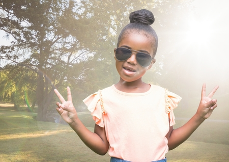 Digital composite of Girl in sunglasses making peace signs against blurry park with flare