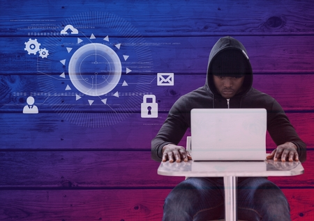 stealer: Digital composite of Hacker using a laptop in front of wood background with digital icons