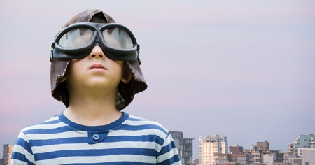 Digital composite of Boy with goggles against buildings and evening sky Stock Photo