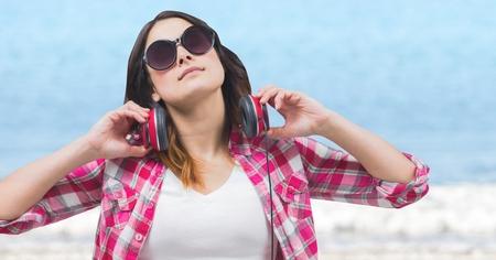 Digitale composiet van Vrouw met koptelefoon zoekt zon tegen wazig water