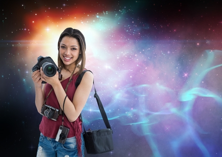 Digital composite of Photographer holding camera  against galaxy background Stock Photo