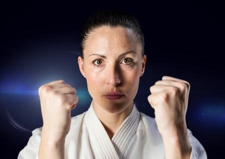 intruder: Digital composite of Woman in karate suit against blue flare