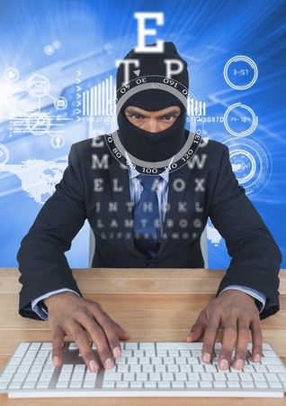 Digital composite of Businessman with hood typing on keyboard in front of blue background with digital letters Stock Photo