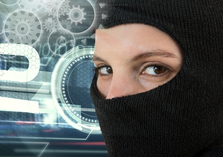 Digital composite of Woman hacker wearing an hood in front of digital background Stock Photo