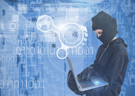 Digital composite of Woman hacker with hood using a laptop in data center Stock Photo