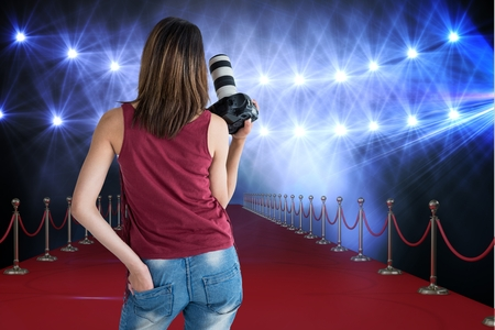 way out: Digital composite of Woman from behind on a red carpet with camera on her hands Stock Photo
